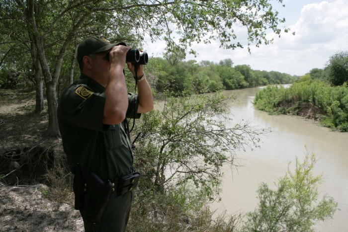 A CBP Border Patrol agent scans the area into Mexico with binoculars looking for illegal immigrants potentially staging to enter the U.S.