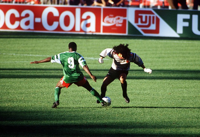 1990 World Cup Finals. Second Phase. Naples, Italy. 23rd June, 1990. Cameroon 2 v Colombia 1. Cameroon's Roger Milla tackles eccentric Colombian goalkeeper Rene Higuita in midfield. Milla won the ball and ran it in to an empty net to score the winning goa