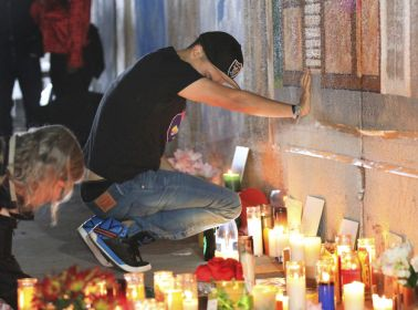 Family and friends of Antonio Ramos grieve during a vigil at the site of the mural project in Oakland, Calif., on Wednesday, Sept. 30, 2015, where Ramos was shot and killed. (Laura A. Oda/Bay Area News Group)