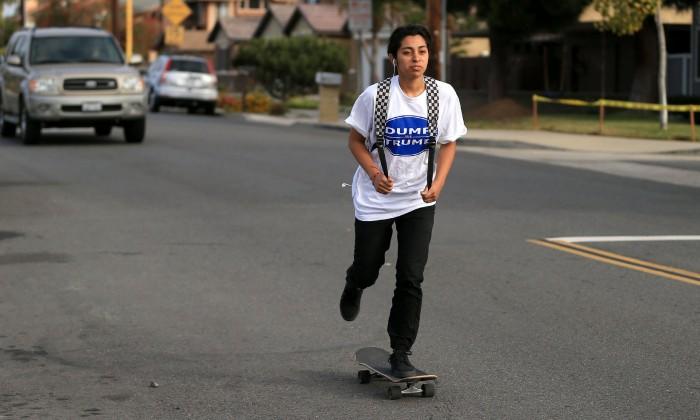 Angelina Alvarez, 16, skateboards to Newport Harbor high school in her Dump Trump shirt. Photo: Daniel A. Anderson
