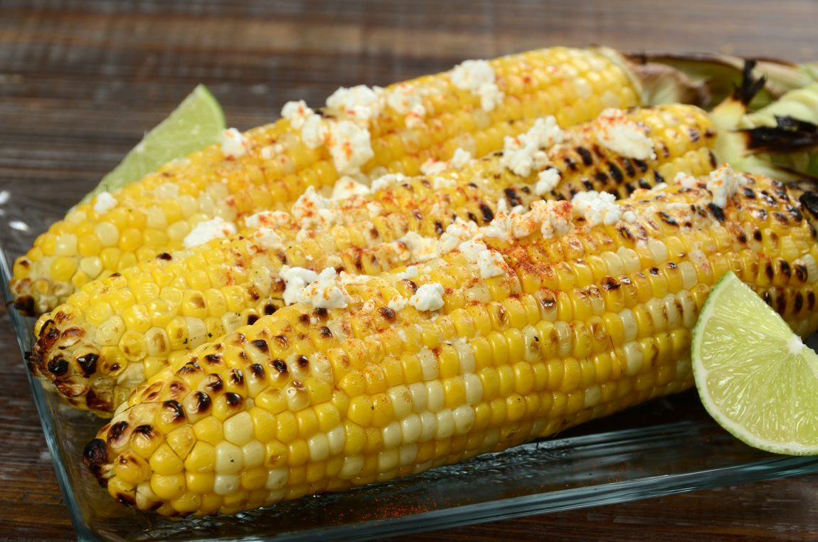 Elote or Mexican grilled corn on the cob served with cotija cheese and ...